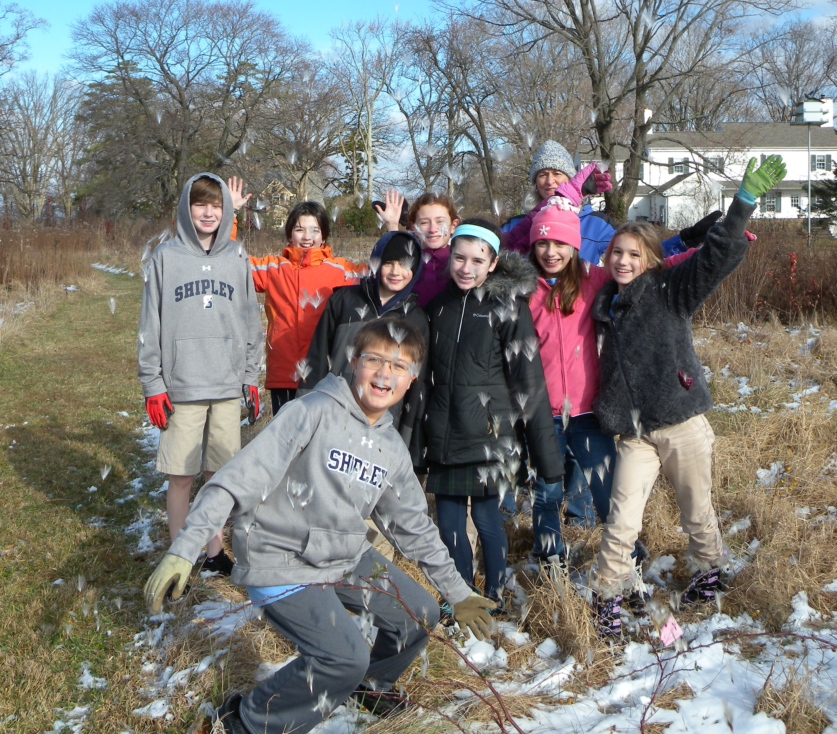 Shipley Service students throwing milkweed seeds into the air.