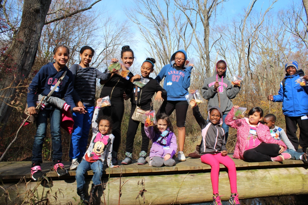 "Melton Center students displaying their ""collection bags"" on the bridge in Rushton Woods, Fall 2014."